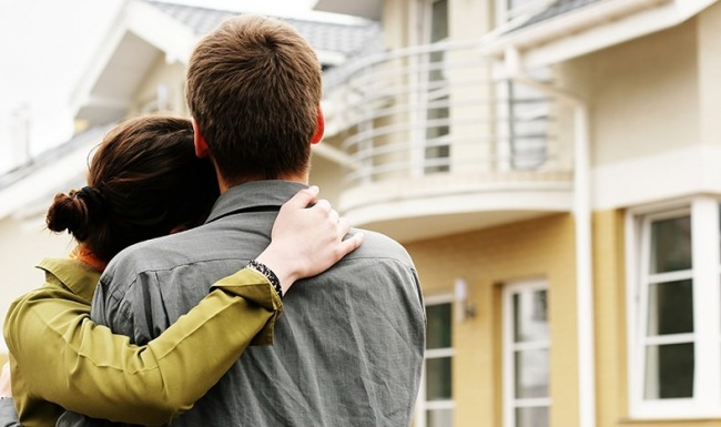 Woman and man embracing in from of house